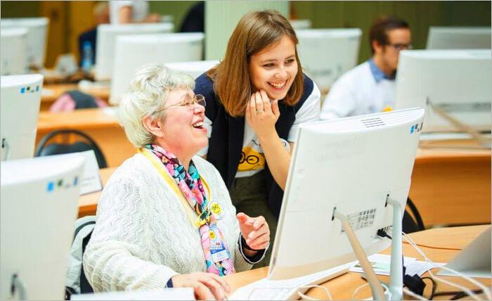 Девочка обучает бабушку работе на компьютере